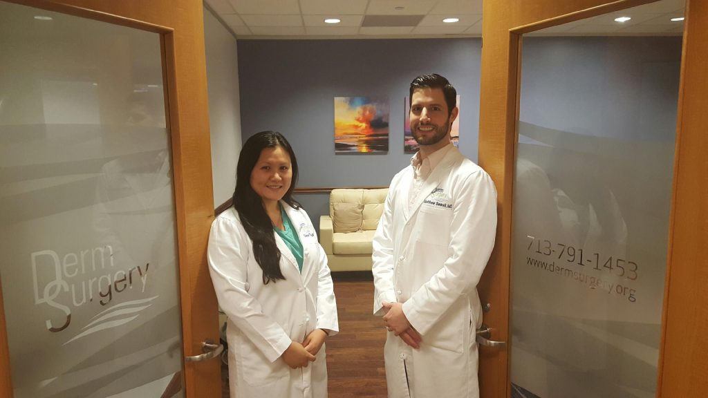 Woman and man in white coats in DermSurgery entryway.
