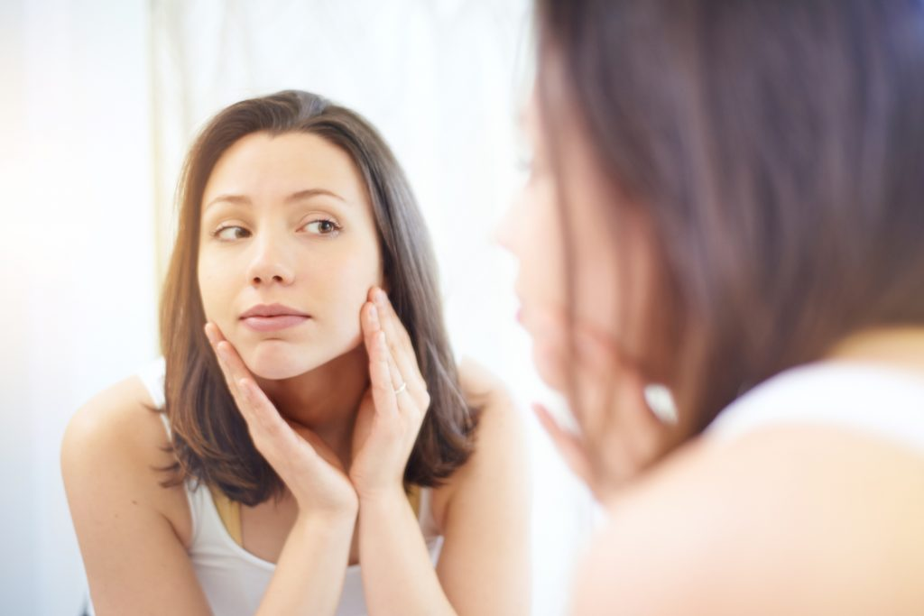 Woman examining her face in the mirror.