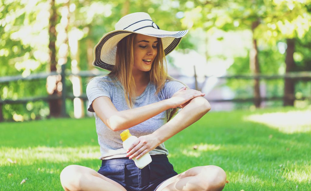Woman in large sun hat on lawn applying sunscreen.