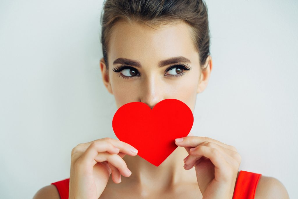 Woman with red heart over her mouth.