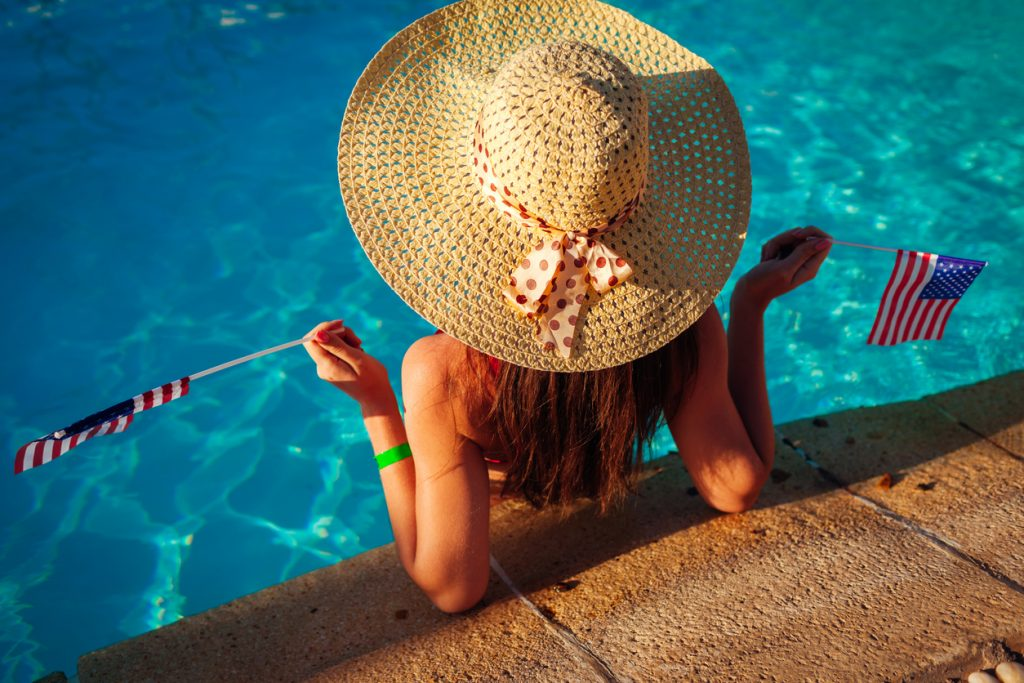 Woman in pool with large sun hat and flags.