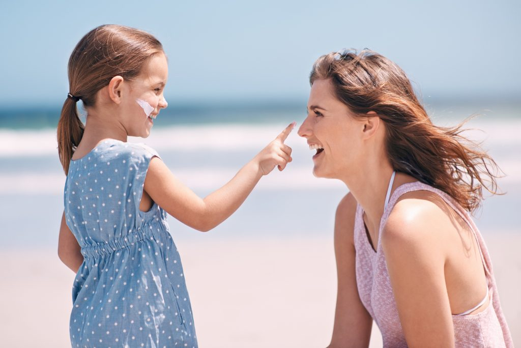 Mother and daughter applying sunscreen.