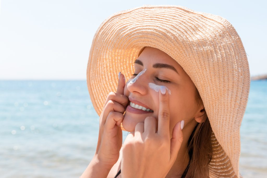 Woman at the beach in large sunhat applying sunscreen.