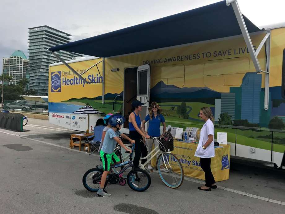 People on bikes in front of mobile healthy skin trailer.