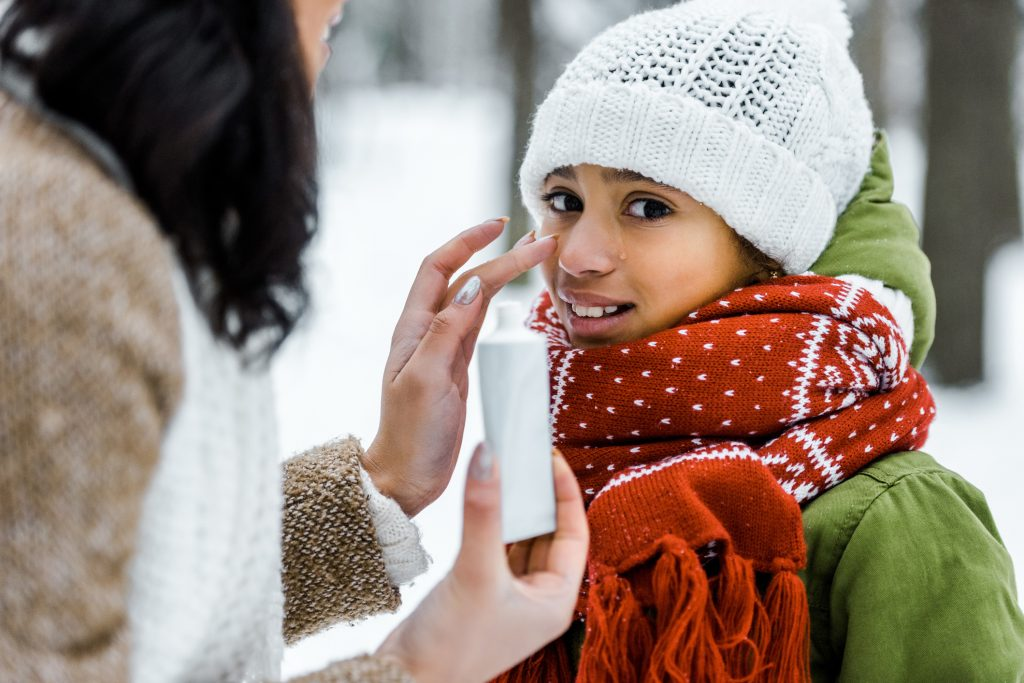 Mom applying sunscreen to daughter's nose in snowy setting.