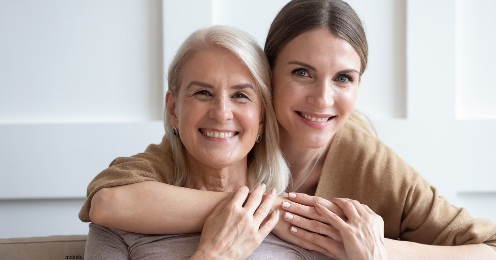 Mother and adult daughter embracing and smiling